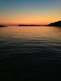 Sonnenuntergang über ruhigem Wasser lizenzfreie stockfotografie