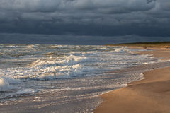 Sonnenuntergang über sandigem Strand und dunkelblauem Himmel vor dem Sturm stockbild