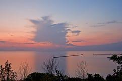 Sonnenuntergang über See mit Bäumen Lizenzfreies Stockfoto