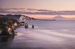 Sonnenuntergang über Seeuferfelsen und Berg Taranaki, Neuseeland Stockbilder