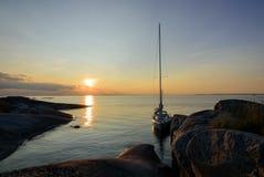 Sonnenuntergang über Segelboot machte lange Seite eine kleine Felseninsel fest Stockbilder