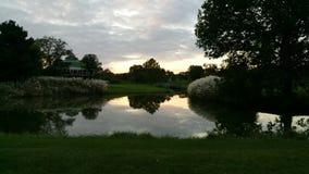 Sonnenuntergang über Teich und See in Nord-Minnesota mit grünem Gras und Bäumen Lizenzfreies Stockbild