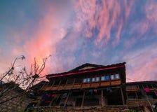 Sonnenuntergang über traditionellem Holzhaus, überraschende Szene mit Himalajabergen himalaja stockfotografie
