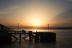 Sonnenuntergang an Almada Quay und 25 De Abril Bridge in Lissabon Stockbilder