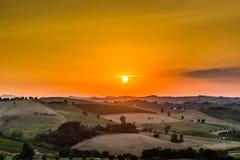 Sonnenuntergang auf üppigem Ackerland in der hügeligen Landschaft Stockfotografie