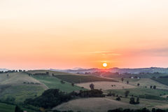 Sonnenuntergang auf üppigem Ackerland in der hügeligen Landschaft Lizenzfreie Stockfotos