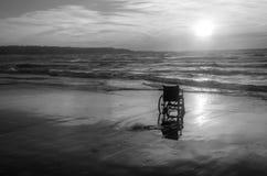 Sonnenuntergang auf dem behinderten Rollstuhl des Strandes Stockfoto