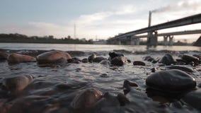 Sonnenuntergang auf dem Fluss unter der Brücke stock footage