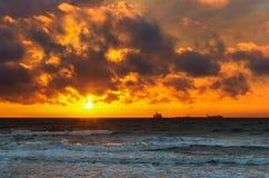 Sonnenuntergang auf dem Meer, der Wellenschlag gegen den Wellenbrecher, das Meer an der Dämmerung, die Schiffe auf dem Horizont Stockfoto