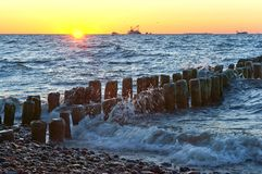 Sonnenuntergang auf dem Meer, der Wellenschlag gegen den Wellenbrecher, das Meer an der Dämmerung, die Schiffe auf dem Horizont Stockfotografie