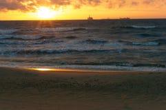 Sonnenuntergang auf dem Meer, der Wellenschlag gegen den Wellenbrecher, das Meer an der Dämmerung, die Schiffe auf dem Horizont Stockfotos