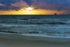 Sonnenuntergang auf dem Meer, der Wellenschlag gegen den Wellenbrecher, das Meer an der Dämmerung, die Schiffe auf dem Horizont Stockbilder
