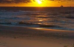 Sonnenuntergang auf dem Meer, der Wellenschlag gegen den Wellenbrecher, das Meer an der Dämmerung, die Schiffe auf dem Horizont Stockbild