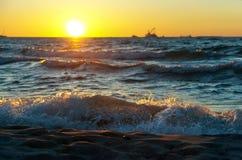 Sonnenuntergang auf dem Meer, der Wellenschlag gegen den Wellenbrecher, das Meer an der Dämmerung, die Schiffe auf dem Horizont Lizenzfreies Stockfoto