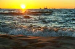 Sonnenuntergang auf dem Meer, der Wellenschlag gegen den Wellenbrecher, das Meer an der Dämmerung, die Schiffe auf dem Horizont Lizenzfreie Stockfotos