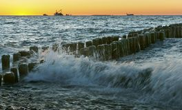 Sonnenuntergang auf dem Meer, der Wellenschlag gegen den Wellenbrecher, das Meer an der Dämmerung, die Schiffe auf dem Horizont Lizenzfreie Stockbilder