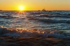 Sonnenuntergang auf dem Meer, der Wellenschlag gegen den Wellenbrecher, das Meer an der Dämmerung, die Schiffe auf dem Horizont Lizenzfreie Stockfotografie