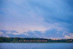 Sonnenuntergang auf dem See in den roten und blauen Farben mit Bäumen Stockfoto