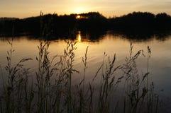 Sonnenuntergang auf dem See im Dorf Lizenzfreie Stockbilder