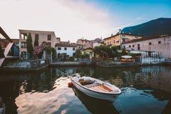 Sonnenuntergang auf dem See Lago di Garda auf der Küste von salo Boot nahe dem Pier auf dem Hintergrund der alten Stadt Stockfotografie