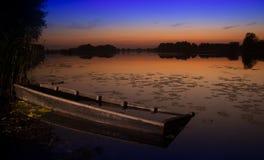 Sonnenuntergang auf dem See mit altem Bootswrack stockfotos