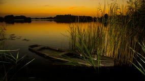 Sonnenuntergang auf dem See mit altem Bootswrack lizenzfreie stockfotos