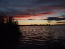 Sonnenuntergang auf dem See und dem Schilf im entfernten Ufer des Hintergrundes lizenzfreies stockbild