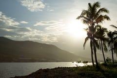Sonnenuntergang auf dem Strand auf einem Hintergrund von Palmen und Bergen Lizenzfreies Stockbild