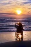 Sonnenuntergang auf dem Strand behinderte Frau im Rollstuhl Lizenzfreie Stockbilder