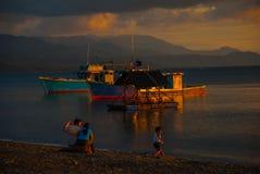 Sonnenuntergang auf dem Strand Leute sitzen auf dem Strand und passen die Schiffe und das Meer auf Pandan, Panay, Philippinen Lizenzfreie Stockfotografie