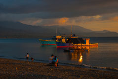 Sonnenuntergang auf dem Strand Leute sitzen auf dem Strand und passen die Schiffe und das Meer auf Pandan, Panay, Philippinen Lizenzfreies Stockfoto