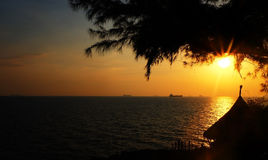 Sonnenuntergang auf dem Strand mit altem Schiff Stockfotografie