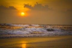 Sonnenuntergang auf dem Strand mit den Wellen, die 2 zerschmettern Lizenzfreie Stockbilder