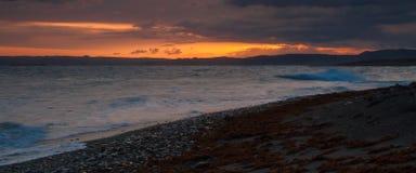 Sonnenuntergang auf dem Strand mit einem schönen hintergrundbeleuchteten Himmel stockbild