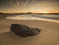 Sonnenuntergang auf dem Strand mit Felsen im Vordergrund Lizenzfreie Stockfotos