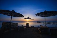 Sonnenuntergang auf dem Strand mit Sonnenschirm Lizenzfreie Stockfotografie