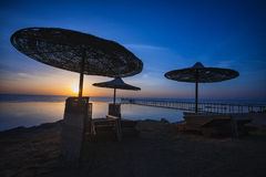 Sonnenuntergang auf dem Strand mit Sonnenschirm Lizenzfreie Stockbilder