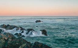Sonnenuntergang auf dem Strand in Südafrika Felsen im Vordergrund Lizenzfreies Stockfoto