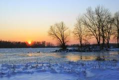 Sonnenuntergang auf dem Ufer des großen Flusses im Winter Stockfotografie