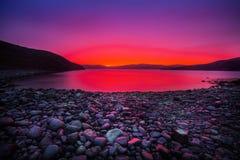 Sonnenuntergang auf der Steinküste stockbild