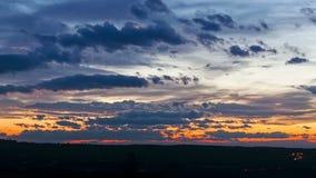 Sonnenuntergang auf einem Feld außerhalb der Stadt mit langsamen Wolken und Verkehr auf Landstraße stock video