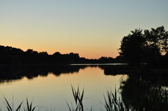 Sonnenuntergang auf einem See in Frankreich mit einem Bauernhof Stockbilder
