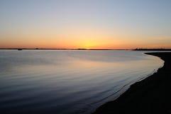 Sonnenuntergang auf einer Flussbank stockbild