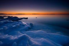 Sonnenuntergang auf eisigem Strand. lizenzfreies stockbild
