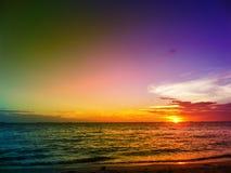Sonnenuntergang auf Horizontlinie über Meer und dunklem buntem Himmel Stockfotos