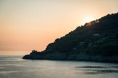 Sonnenuntergang auf Mittelmeer, kleine Kapelle auf den Felsen, Ligurien, Italien lizenzfreie stockbilder