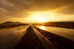 Sonnenuntergang auf nasser Straße Lizenzfreies Stockfoto