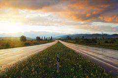 Sonnenuntergang auf nasser Straße Lizenzfreie Stockfotos