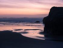 Sonnenuntergang auf Ozeanstrand mit Klippen Stockbild
