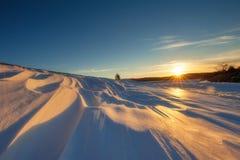 Sonnenuntergang auf schneebedecktem Feld Stockfoto
